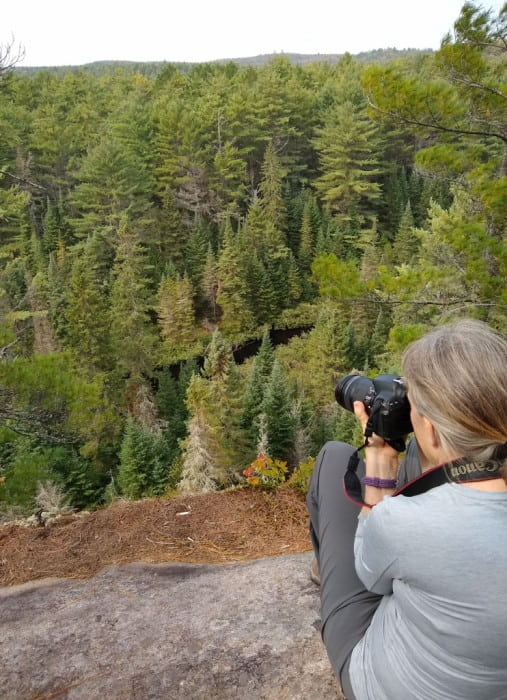 Person with camera on North Madawaska River and forest