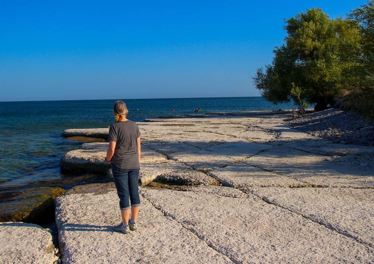 Woman on rock ledge Prince Edward Point Beach