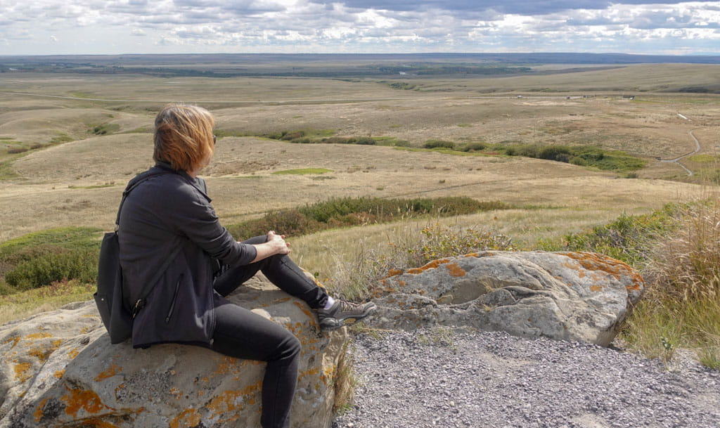 Person on rock looking out to Oldman River Valley