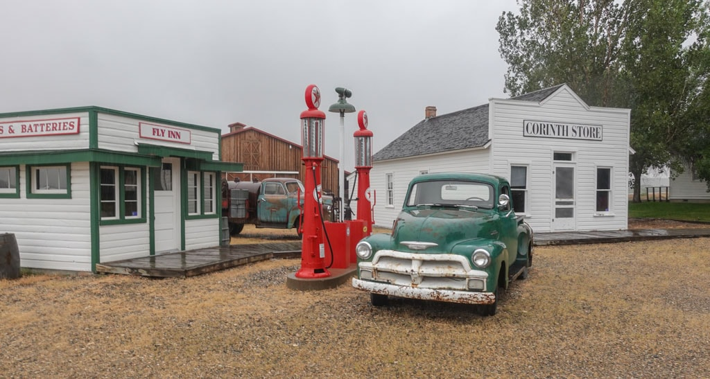 Antique Truck at old gas pumps with 3 relocated building as background