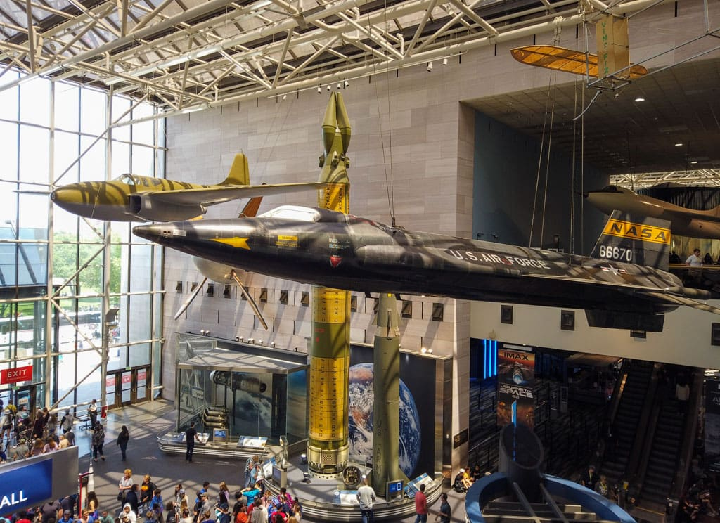Museum visitors under aircraft hanging from ceiling, displ