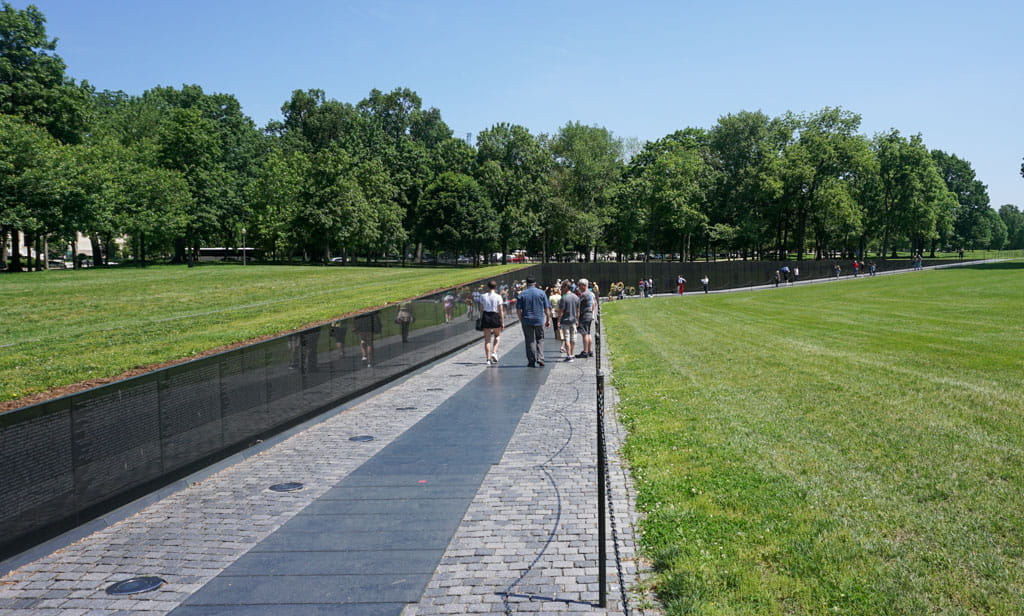 People along black marble walls Vietnam Veterans Memorial