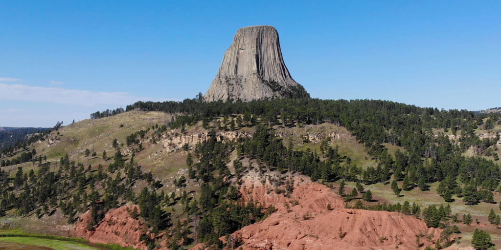 Red sandstone cliffs with Devils Tower in background