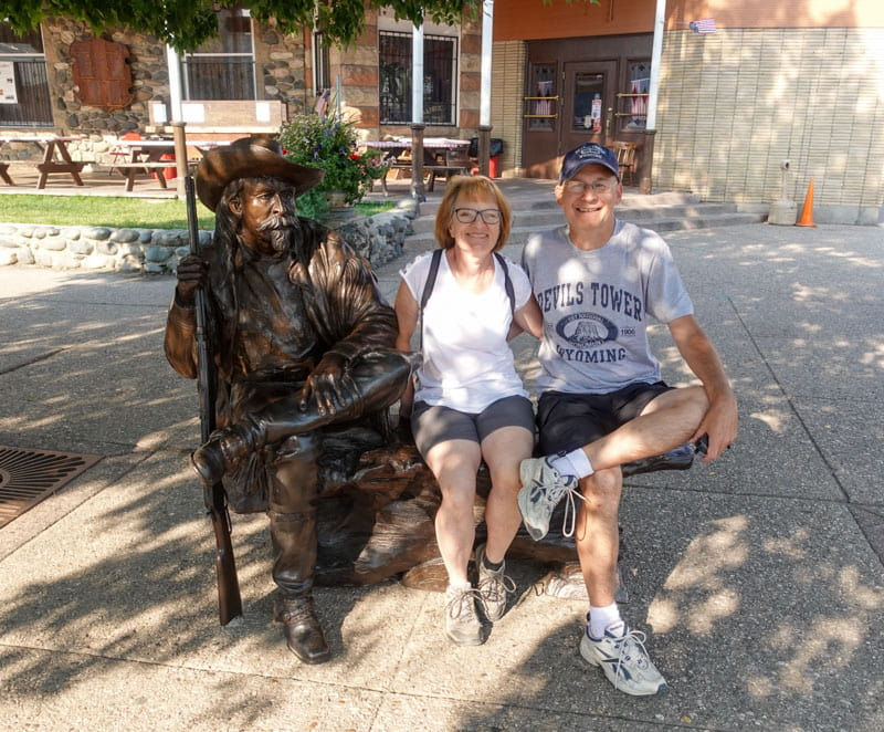 Statue Buffalo Bill, woman, man on bench