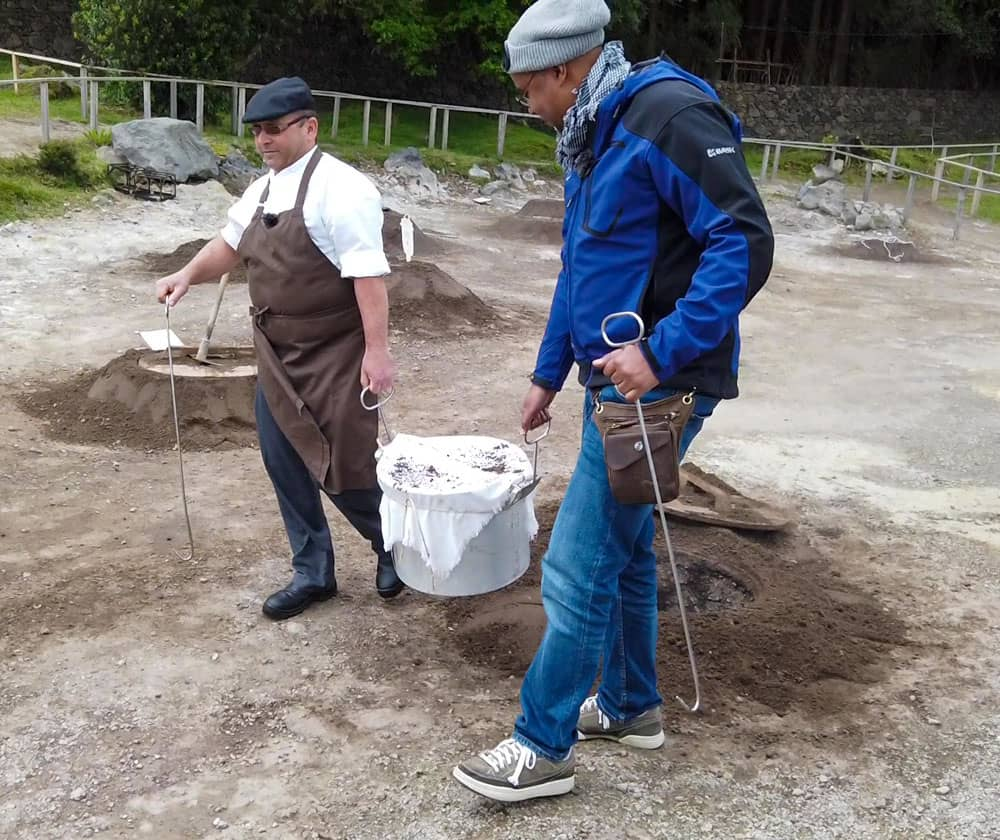2 men carry covered pot from hole Furnas Lake Caldera