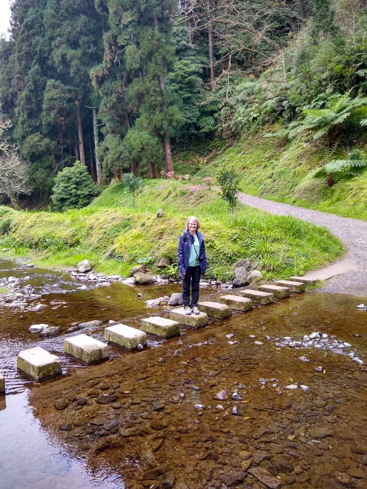 Woman on river stepping stones Furnas Lake trail