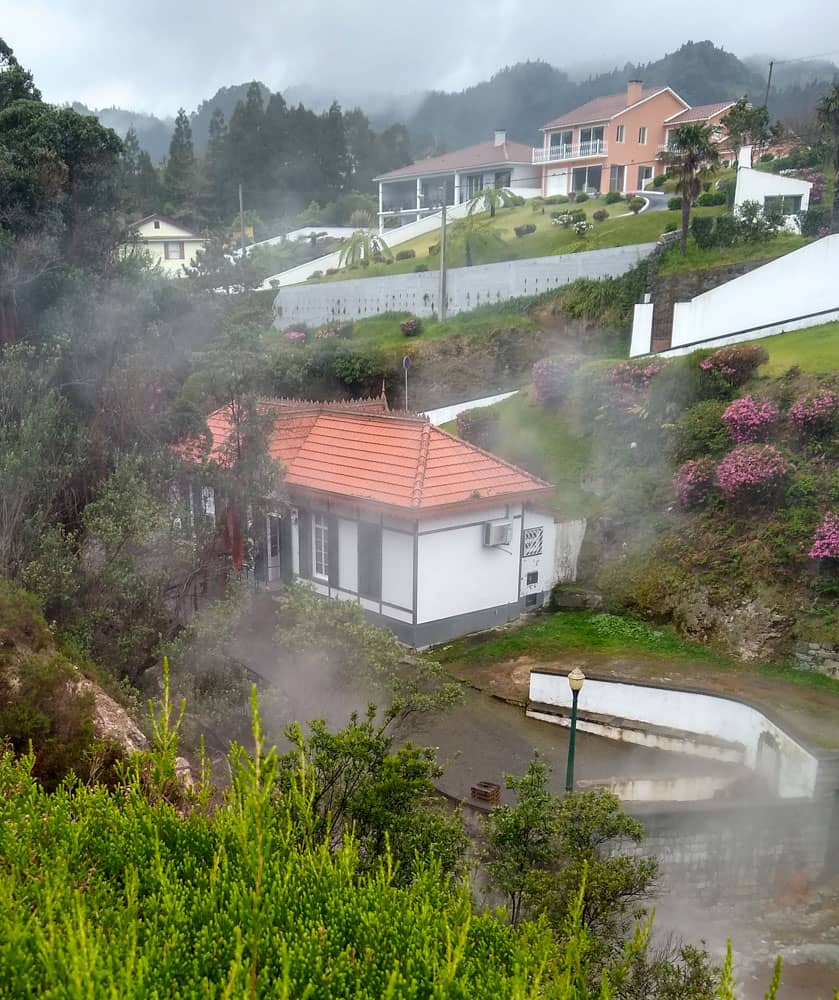 Lower white building amid rising steam Furnas Caldeira
