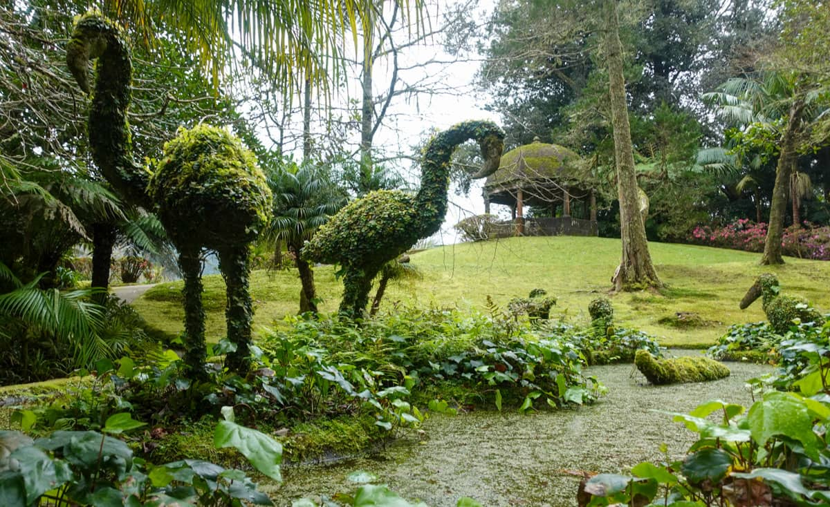 2 large plants shaped like birds in topiary garden