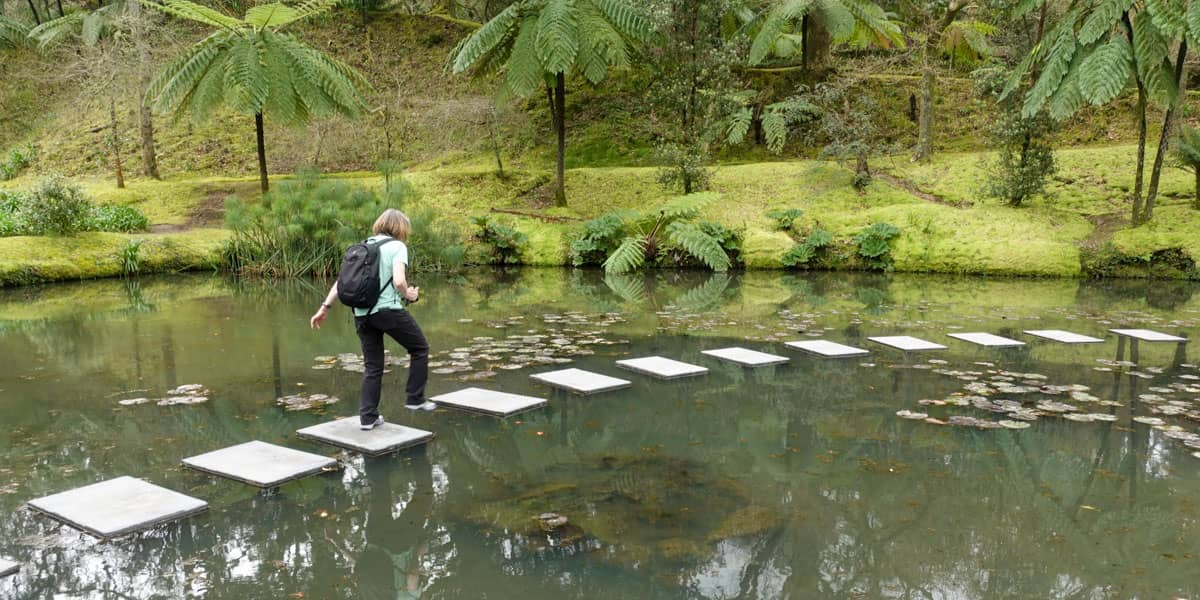 Person walking stepping stones in pond