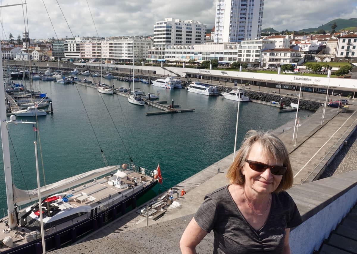 Woman Ponta Delgada city and marina behind