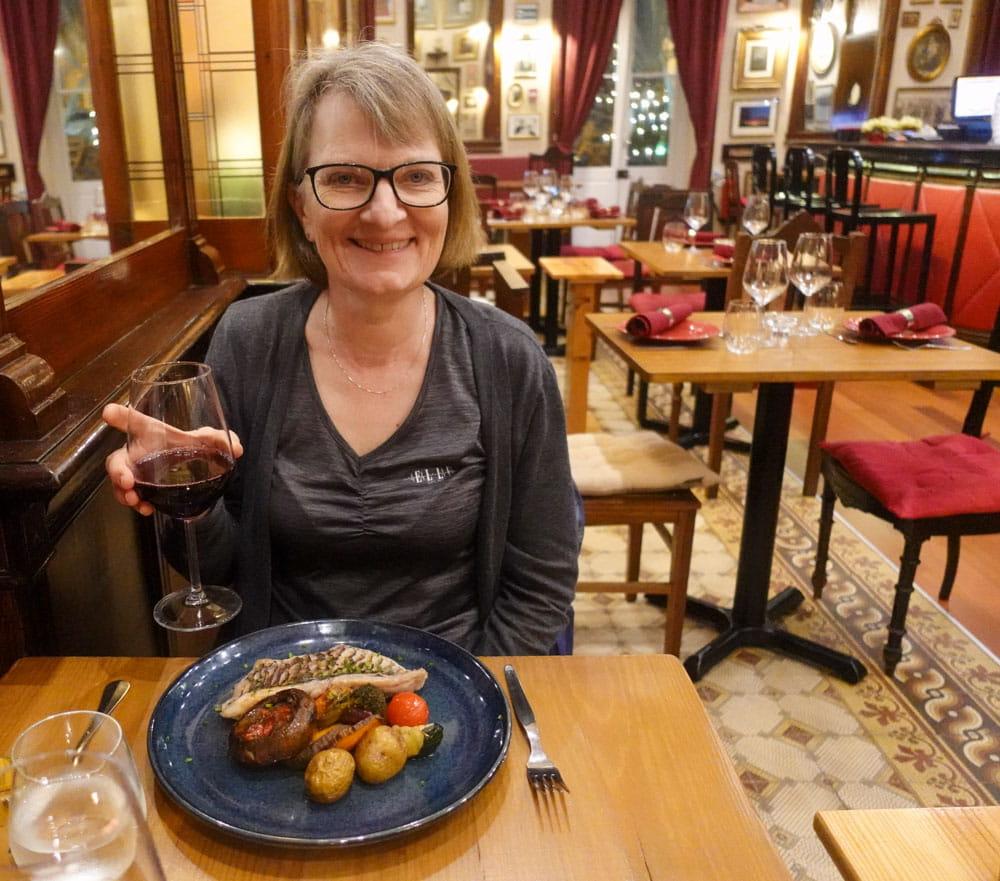 Woman holding wine glass in Singular Bistro