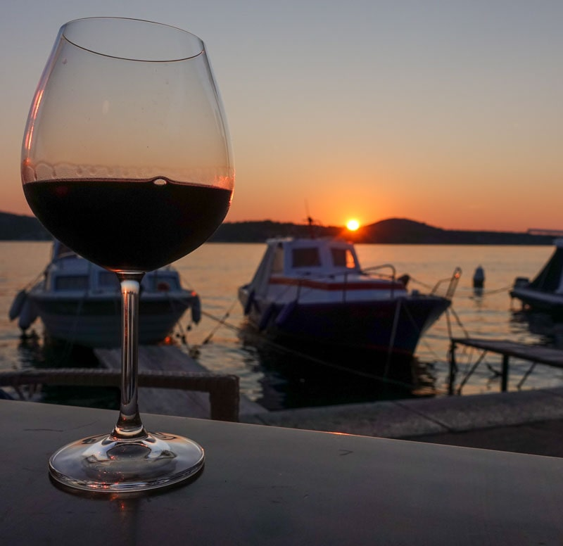 Wine glass and sunset on Sibenik harbour