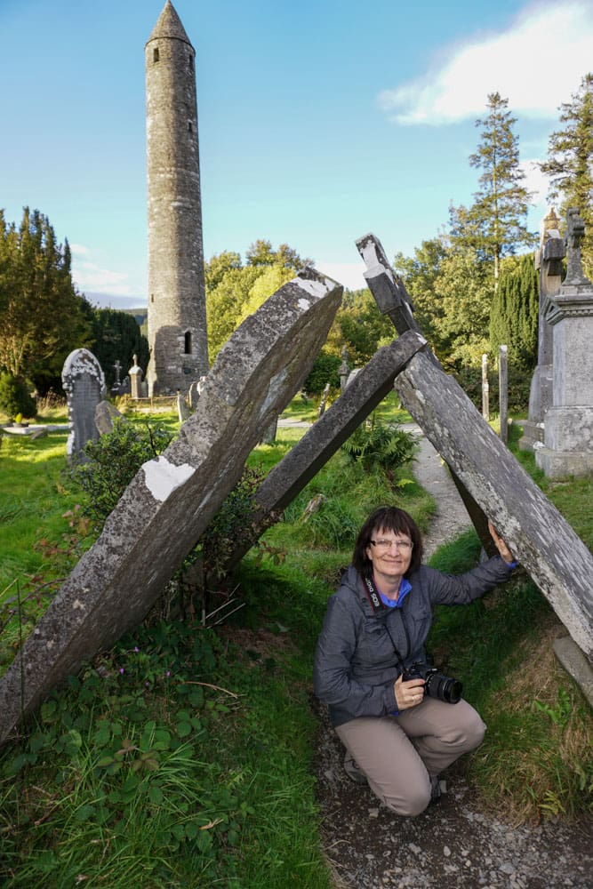 Woman crouching under gravestones tipped against each otherGlendalough Roun