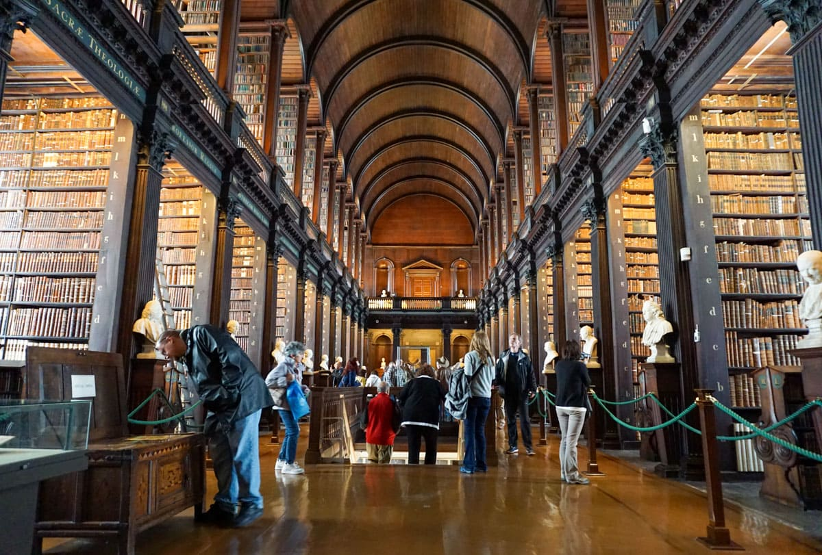People in central barrel-shaped room Trinity College Long Room