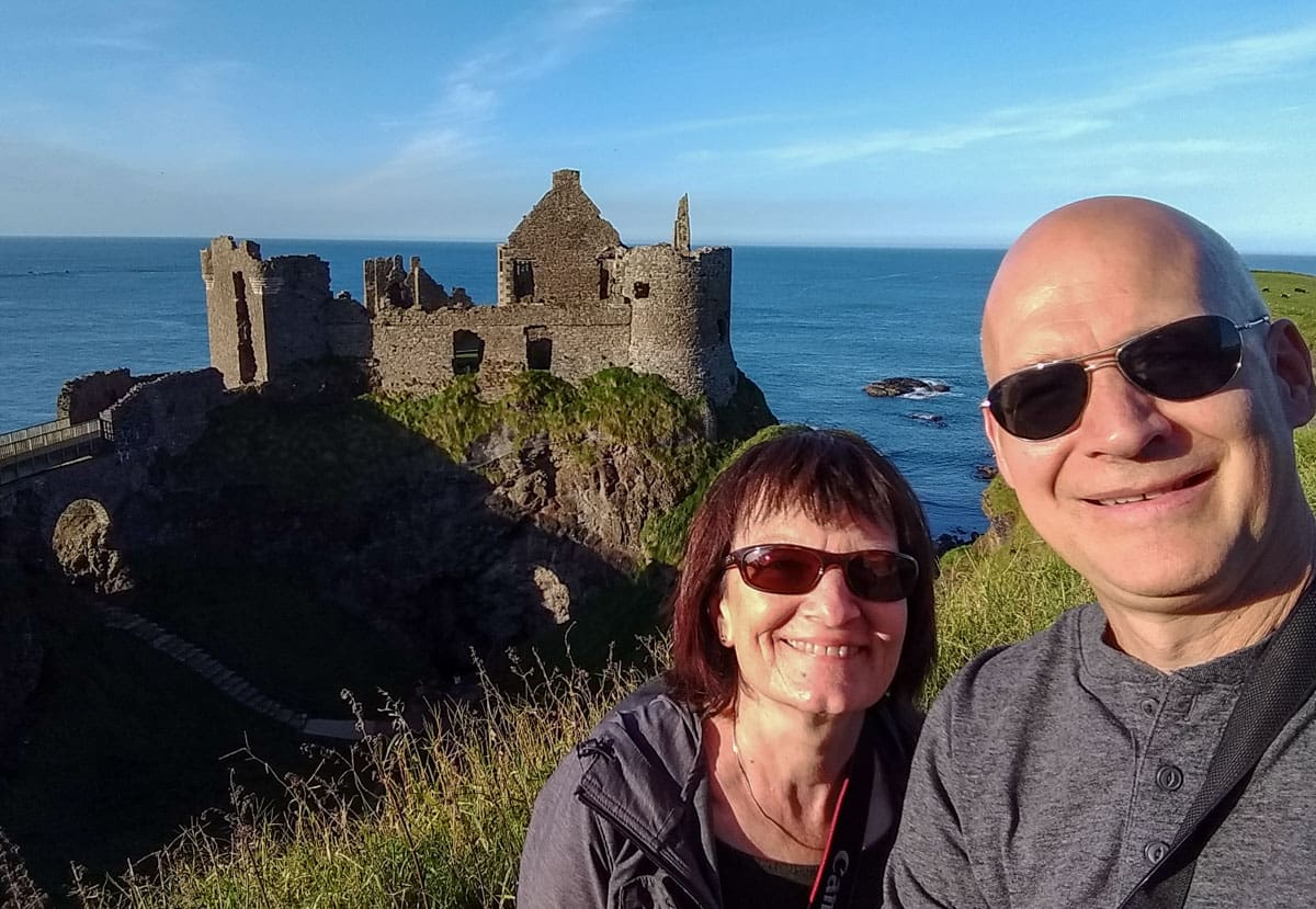 Couple with Dunluce Castle and ocean background