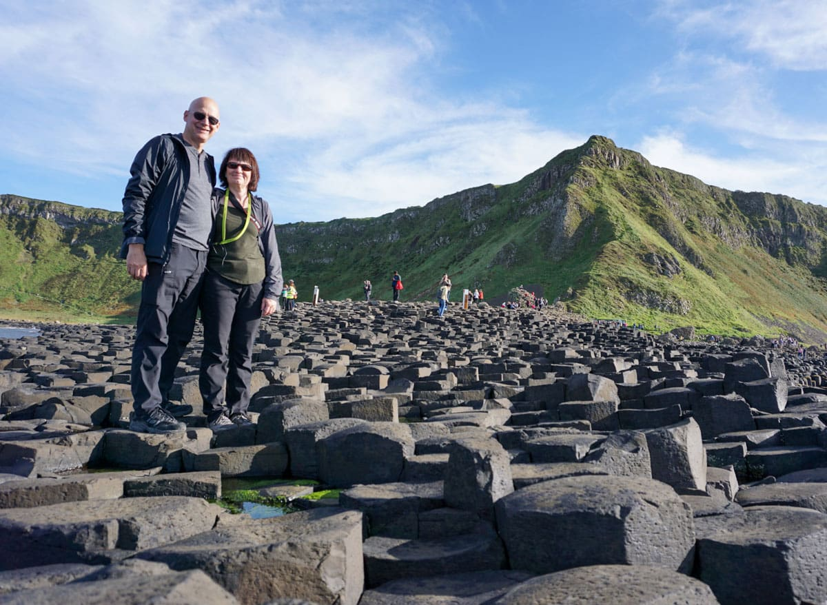 Couple on basalt rocks of Ireland's Giant's Causeway