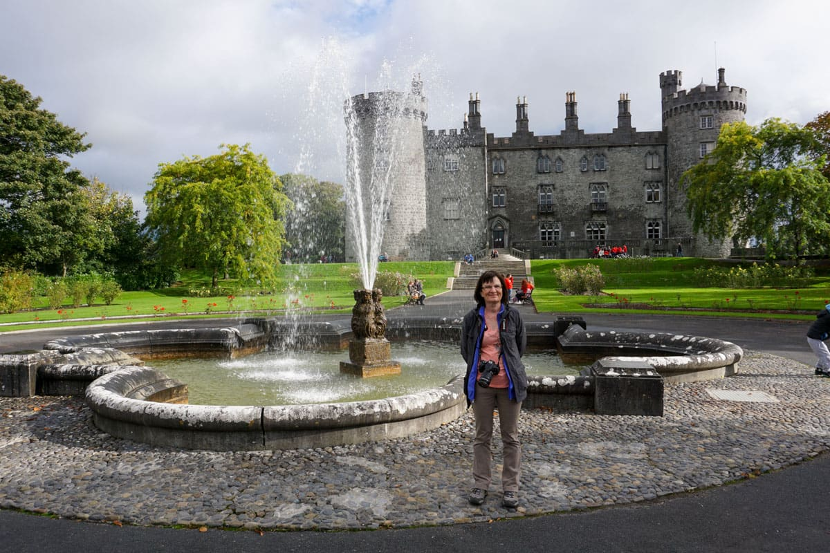 Person with Kilkenny Castle fountain behind