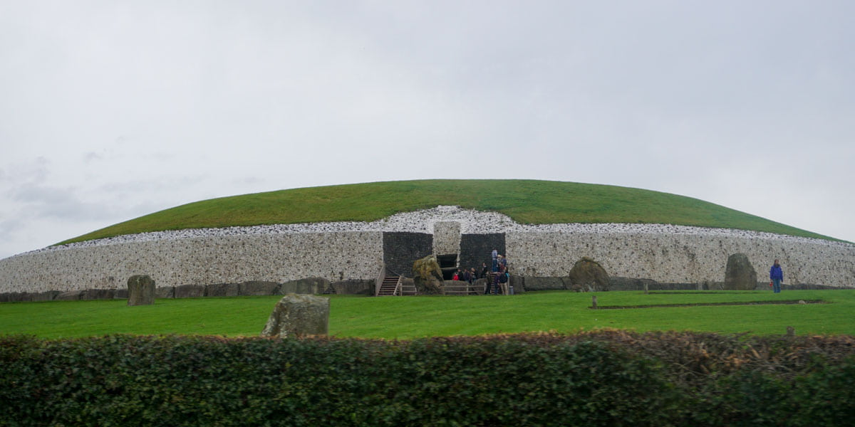 Large grassed mound stoneworked sides Newgrange Ireland